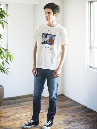 Cómo combinar: tenis de lona en negro y blanco, vaqueros azul marino, camiseta con cuello circular estampada blanca