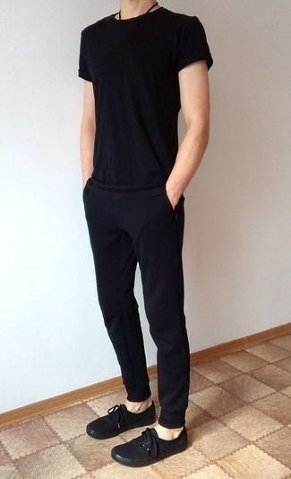 Combinar un pantalón de chándal negro: Considera ponerse una camiseta con cuello circular negra y un pantalón de chándal negro transmitirán una vibra libre y relajada. ¿Te sientes valiente? Opta por un par de tenis de lona negros.
