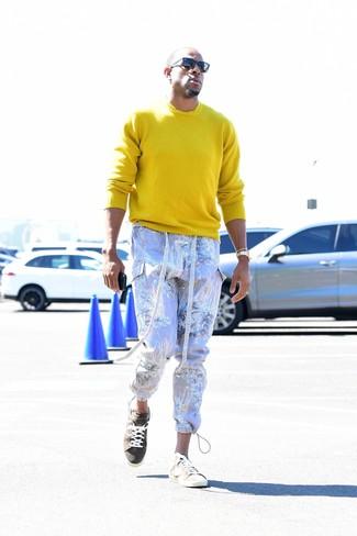 Cómo combinar: gafas de sol negras, tenis de ante en beige, pantalón cargo estampado violeta claro, jersey con cuello circular amarillo