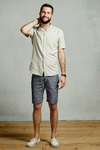 Cómo combinar: pulsera de cuero en marrón oscuro, tenis de lona en beige, pantalones cortos estampados azules, camisa de manga corta en verde menta