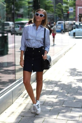 Cómo combinar: bolso bandolera de cuero negro, tenis de cuero en blanco y negro, falda con botones negra, camisa de vestir de rayas verticales celeste