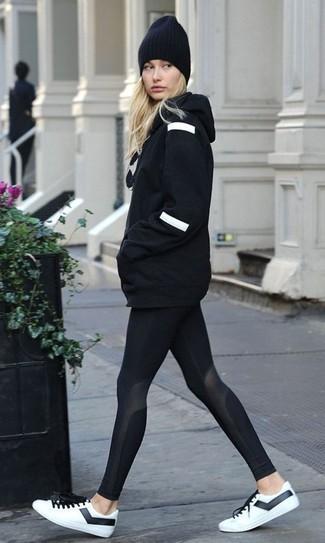 Cómo combinar: gorro negro, tenis de cuero en blanco y negro, leggings negros, sudadera con capucha negra