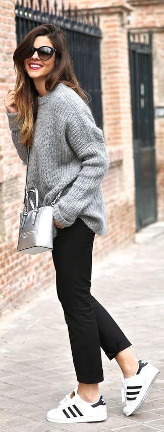 Cómo combinar: bolso bandolera de cuero plateado, tenis de cuero en blanco y negro, pantalón chino negro, jersey oversized de punto gris