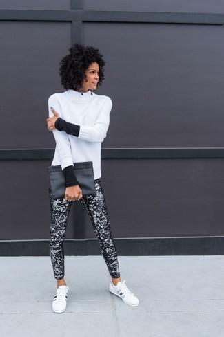 Cómo combinar: cartera sobre de cuero negra, tenis de cuero en blanco y negro, pantalones pitillo de lentejuelas negros, jersey de cuello alto de lana de punto blanco
