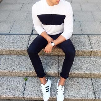 Cómo combinar: reloj de cuero negro, tenis de cuero en blanco y negro, vaqueros pitillo negros, jersey con cuello circular en blanco y negro