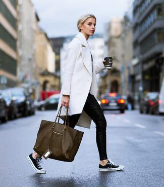 Cómo combinar: bolsa tote de cuero verde oliva, tenis de lona en negro y blanco, pantalones pitillo negros, abrigo blanco