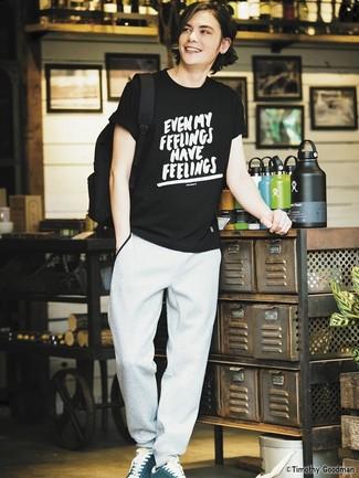 Cómo combinar: mochila de lona negra, tenis de ante en verde azulado, pantalón de chándal gris, camiseta con cuello circular estampada en negro y blanco