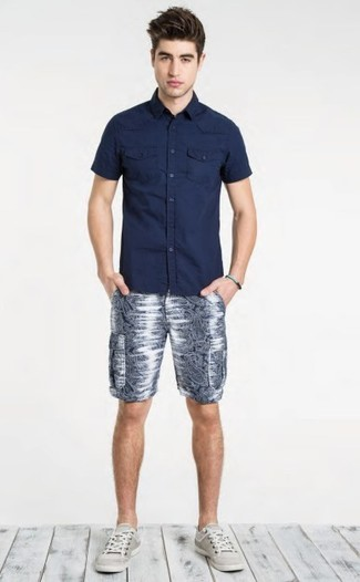Cómo combinar: tenis grises, pantalones cortos estampados azul marino, camisa de manga corta azul marino