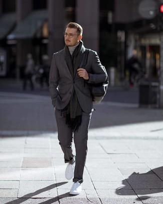 Cómo combinar: mochila de cuero negra, tenis blancos, jersey de cuello alto gris, traje de rayas verticales en gris oscuro