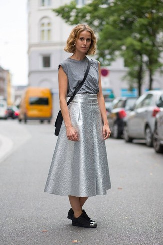 Cómo combinar: bolso bandolera de cuero negro, tenis de ante negros, falda campana plateada, camiseta sin manga gris