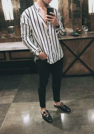 Cómo combinar: reloj de cuero negro, tenis de cuero negros, vaqueros pitillo negros, camisa de manga larga de rayas verticales en blanco y negro