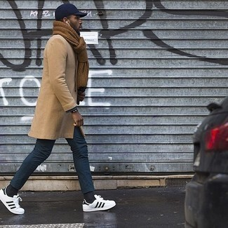 Combinar unos tenis de cuero en blanco y negro: Considera ponerse un abrigo largo marrón claro y un pantalón chino azul marino para un lindo look para el trabajo. Para el calzado ve por el camino informal con tenis de cuero en blanco y negro.