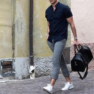 Cómo combinar: bolsa de viaje de cuero negra, tenis de cuero blancos, pantalón chino gris, camisa de manga corta azul marino
