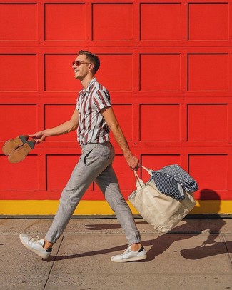 Cómo combinar: bolsa tote de lona en beige, tenis de cuero blancos, pantalón chino de lino en beige, camisa de manga corta de rayas verticales en blanco y rojo