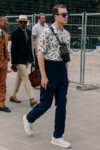 Cómo combinar: riñonera de cuero negra, tenis de cuero blancos, pantalón chino azul marino, camisa de manga corta estampada en blanco y azul marino