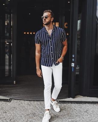 Cómo combinar: gafas de sol negras, tenis de cuero blancos, pantalón chino blanco, camisa de manga corta de rayas verticales en azul marino y blanco