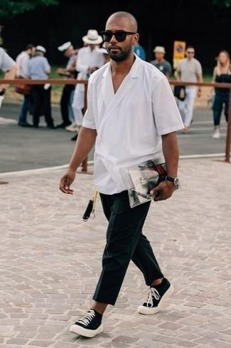 Outfits hombres: Empareja una camisa de manga corta blanca junto a un pantalón chino azul marino para lidiar sin esfuerzo con lo que sea que te traiga el día. Tenis de lona en negro y blanco son una opción atractiva para complementar tu atuendo.