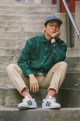 Cómo combinar: gorra de béisbol gris, tenis de cuero de rayas horizontales en blanco y negro, pantalón chino en beige, camisa de manga larga de rayas verticales verde oscuro