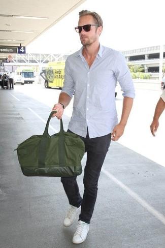 Cómo combinar: bolsa de viaje de lona verde oliva, tenis de cuero blancos, pantalón chino negro, camisa de manga larga celeste