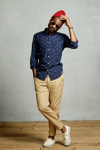 Cómo combinar: gorro rojo, tenis de lona blancos, pantalón chino marrón claro, camisa de manga larga estampada azul marino