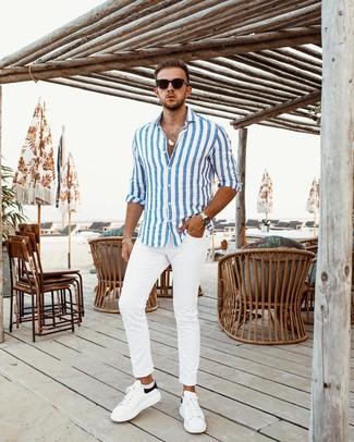 Cómo combinar: gafas de sol negras, tenis de cuero en blanco y negro, pantalón chino blanco, camisa de manga larga de rayas verticales en blanco y azul