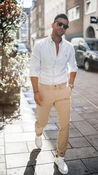 Combinar un pantalón chino marrón claro: Usa una camisa de manga larga de rayas verticales blanca y un pantalón chino marrón claro para conseguir una apariencia relajada pero elegante. Tenis de cuero blancos son una opción buena para complementar tu atuendo.