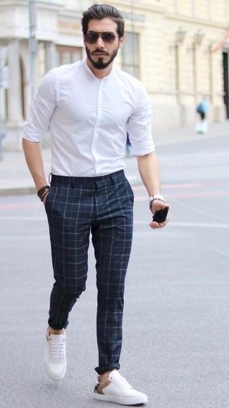 Combinar una camisa de manga larga blanca: Para un atuendo que esté lleno de caracter y personalidad intenta combinar una camisa de manga larga blanca junto a un pantalón chino a cuadros azul marino. Tenis de cuero blancos son una opción grandiosa para complementar tu atuendo.