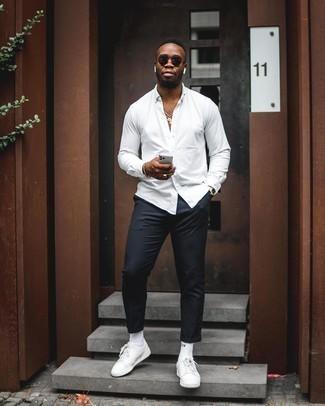 Combinar un pantalón chino negro: Casa una camisa de manga larga blanca con un pantalón chino negro para una vestimenta cómoda que queda muy bien junta. Mezcle diferentes estilos con tenis de cuero blancos.