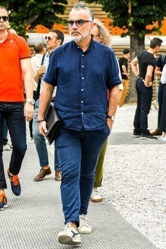 Combinar un bolso con cremallera de cuero negro: Una camisa de manga larga de cambray azul marino y un bolso con cremallera de cuero negro son tu atuendo para salir los días de descanso. Complementa tu atuendo con tenis de lona en blanco y azul marino para mostrar tu inteligencia sartorial.