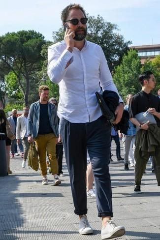 Combinar un bolso con cremallera de lona azul marino: Una camisa de manga larga blanca y un bolso con cremallera de lona azul marino son una gran fórmula de vestimenta para tener en tu clóset. Usa un par de tenis de lona blancos para mostrar tu inteligencia sartorial.