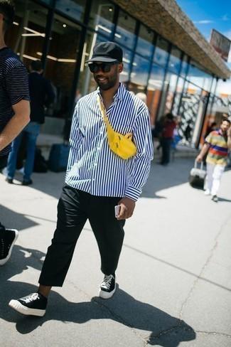 Outfits hombres: Para crear una apariencia para un almuerzo con amigos en el fin de semana opta por una camisa de manga larga de rayas verticales en blanco y azul marino y un pantalón chino negro. Tenis de lona en negro y blanco son una opción atractiva para completar este atuendo.
