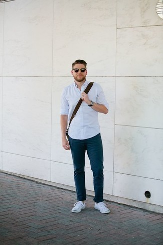 Outfits hombres: Equípate una camisa de manga larga celeste con un pantalón chino azul marino para un look diario sin parecer demasiado arreglada. Si no quieres vestir totalmente formal, haz tenis de lona blancos tu calzado.