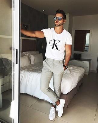 Cómo combinar: gafas de sol negras, tenis de cuero blancos, pantalón chino en beige, camiseta con cuello circular estampada en blanco y negro