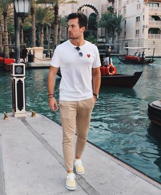 Cómo combinar: gafas de sol negras, tenis de lona amarillos, pantalón chino marrón claro, camiseta con cuello circular blanca