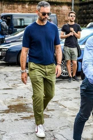 Combinar una camiseta con cuello circular azul marino: Intenta combinar una camiseta con cuello circular azul marino junto a un pantalón chino verde oliva para cualquier sorpresa que haya en el día. Tenis en blanco y rojo son una opción muy buena para completar este atuendo.