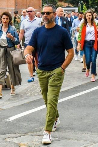 Combinar una camiseta con cuello circular azul marino: Utiliza una camiseta con cuello circular azul marino y un pantalón chino verde oliva para un look diario sin parecer demasiado arreglada. Tenis de cuero en blanco y rojo son una opción excelente para complementar tu atuendo.