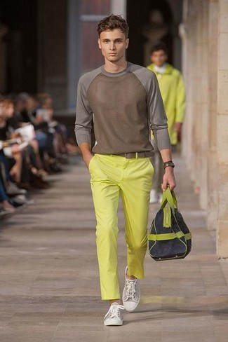 Cómo combinar: bolso baúl de lona azul marino, tenis de lona grises, pantalón chino amarillo, jersey con cuello circular marrón