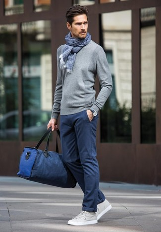 Cómo combinar: bolsa de viaje de lona azul marino, tenis de cuero grises, pantalón chino azul marino, jersey con cuello circular gris