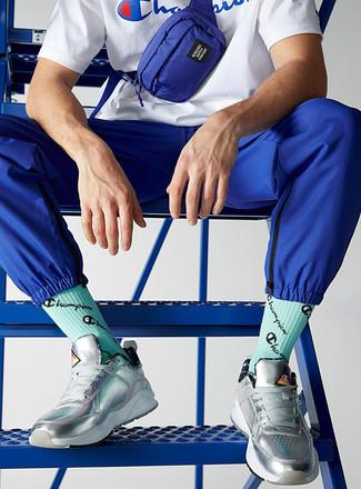 Cómo combinar: riñonera de lona azul, tenis de cuero plateados, pantalón de chándal azul, camiseta con cuello circular estampada en blanco y azul