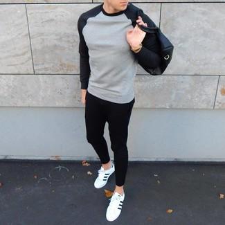 Cómo combinar: bolsa de viaje de cuero negra, tenis de cuero en blanco y negro, pantalón de chándal negro, sudadera gris