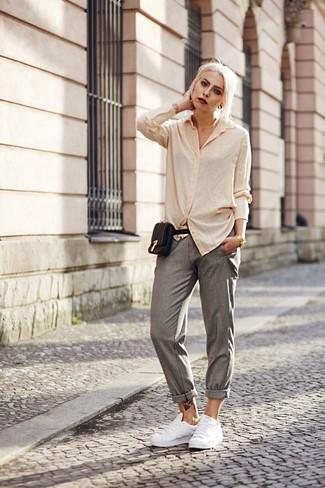 Cómo combinar: riñonera de cuero negra, tenis de cuero blancos, pantalón de pinzas gris, camisa de vestir en beige