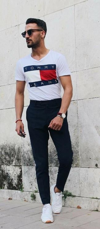 Cómo combinar: gafas de sol negras, tenis de cuero blancos, pantalón de vestir negro, camiseta con cuello circular estampada blanca