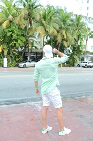 Cómo combinar: gorra de béisbol blanca, tenis de cuero blancos, pantalones cortos blancos, camisa de manga larga en verde menta