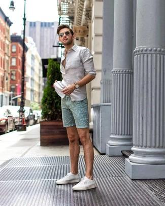 Cómo combinar: gafas de sol negras, tenis de lona blancos, pantalones cortos estampados en verde menta, camisa de manga larga de lino blanca