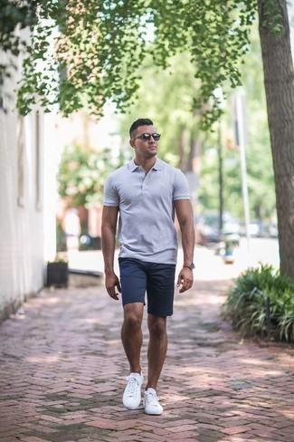 Combinar unos pantalones cortos azul marino: Ponte una camisa polo gris y unos pantalones cortos azul marino para una apariencia fácil de vestir para todos los días. Tenis de lona blancos son una opción inigualable para complementar tu atuendo.