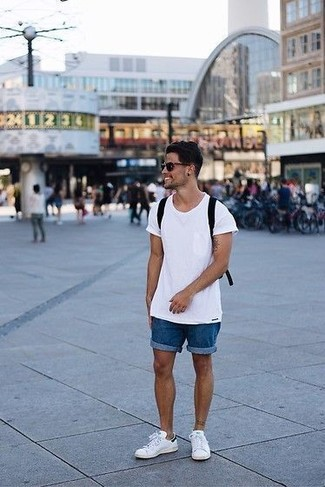 Cómo combinar: mochila de lona negra, tenis de cuero blancos, pantalones cortos vaqueros azules, camiseta con cuello circular blanca