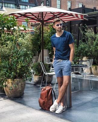 Cómo combinar: mochila de cuero marrón, tenis blancos, pantalones cortos azules, camiseta con cuello circular azul marino