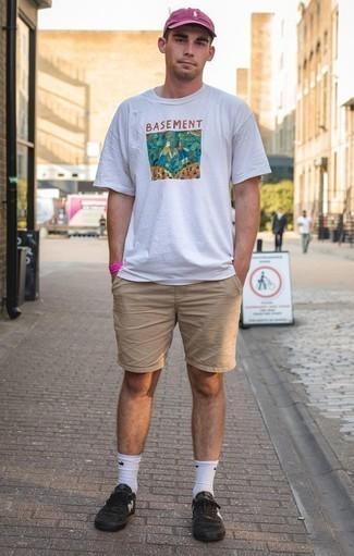 Combinar unos pantalones cortos marrón claro: Empareja una camiseta con cuello circular estampada blanca con unos pantalones cortos marrón claro para un look agradable de fin de semana. Complementa tu atuendo con tenis de lona negros.