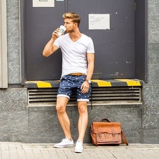 Cómo combinar: bolso mensajero de cuero marrón claro, tenis de lona blancos, pantalones cortos estampados azul marino, camiseta con cuello en v blanca