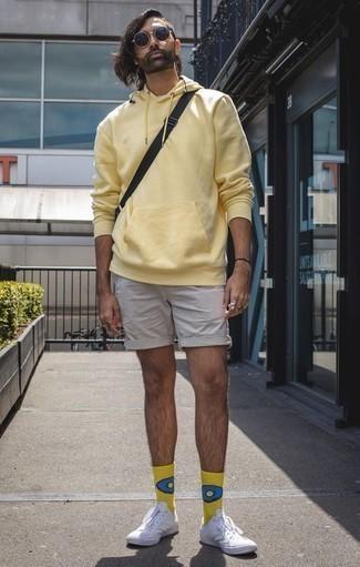 Combinar unos pantalones cortos en beige: Empareja una sudadera con capucha amarilla con unos pantalones cortos en beige para un almuerzo en domingo con amigos. Tenis de lona blancos son una opción muy buena para complementar tu atuendo.